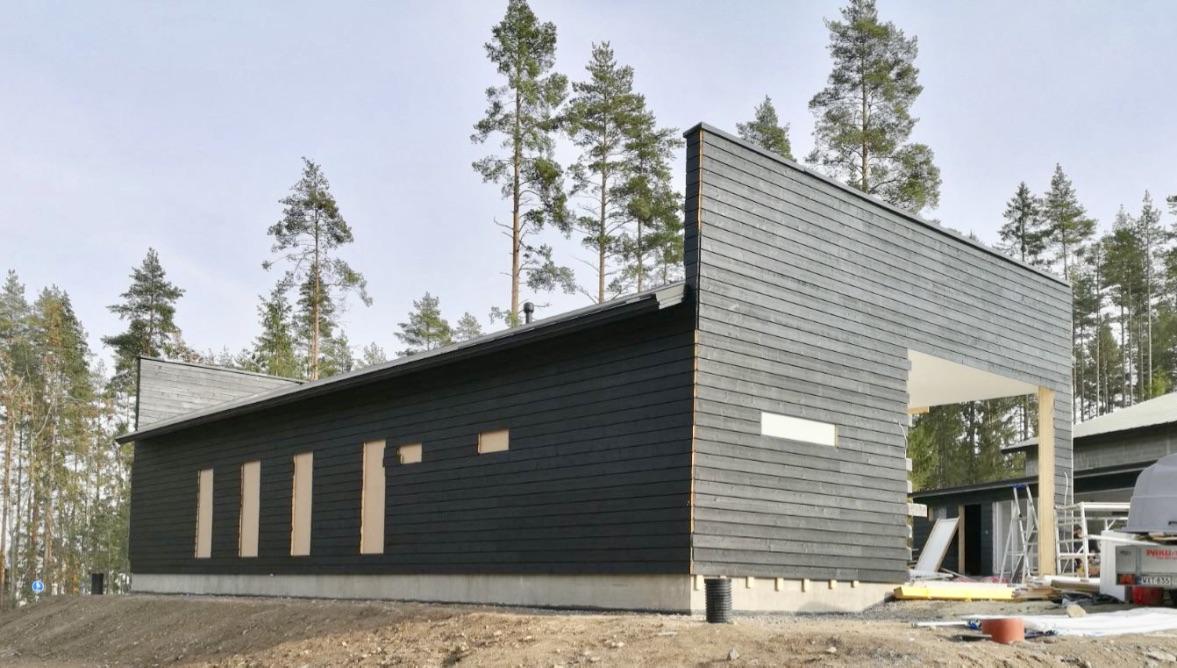 Kylätimpureiden rakentama yksikerroksisen omakotitalon musta julkisivu rakennusvaiheessa