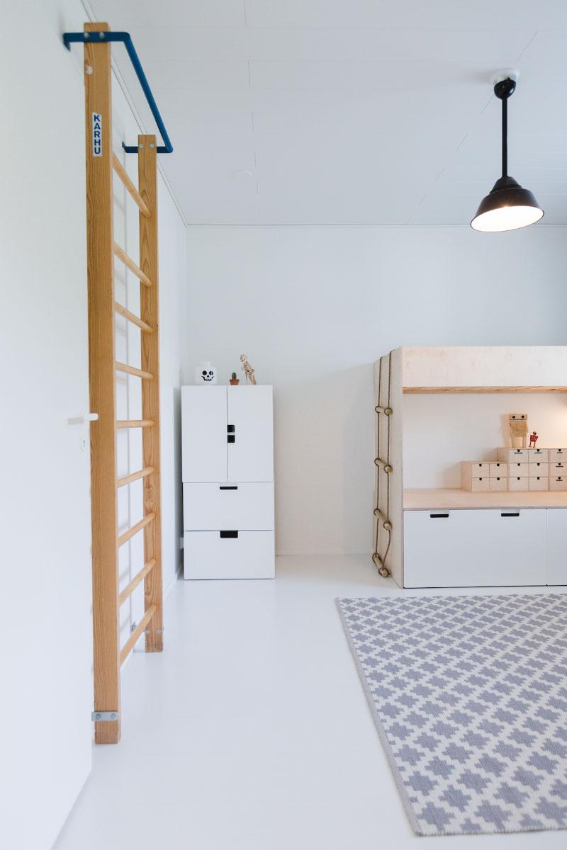 Omakotitalon valkoinen lastenhuone jonka seinällä puolapuut ja toisessa nurkassa vaalea kerrossänky.