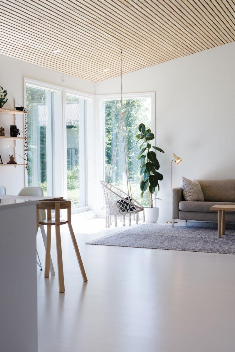 Omakotitalon harmoninen ja vaalea olohuone, skandinaavisesti sisustettuna.
